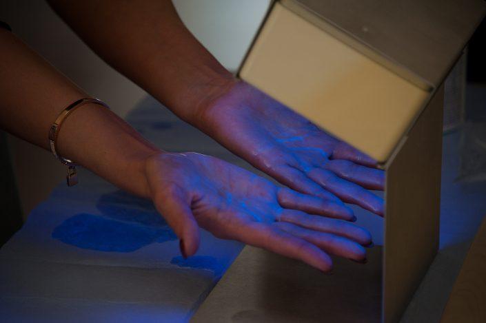 Darstellung Händedesinfektion mit der Schwarzlicht Lampe